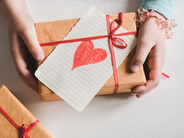 Kleine tochter, die ein geschenk anhält