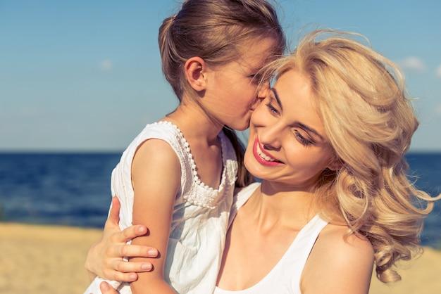 Kleine tochter küsst mutter am strand.