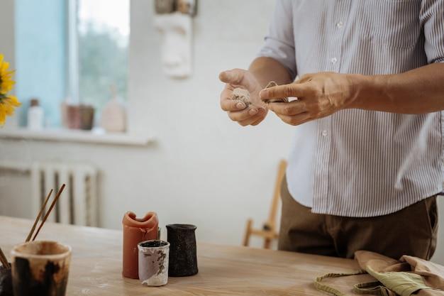 Kleine töpfe. kreativer professioneller handwerker, der kleine töpfe für zimmerpflanzen macht, während er hart arbeitet