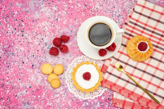 Kleine torte der oberen entfernten ansicht mit frischen himbeeren der sahnekekse zusammen mit einer tasse kaffee auf der farbigen teefarbe der oberfläche