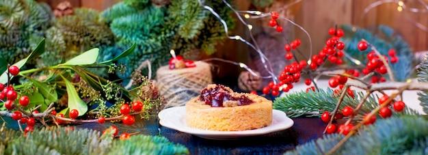 Kleine torte mit preiselbeeren marmelade auf einem blauen hölzernen weihnachtsbaum