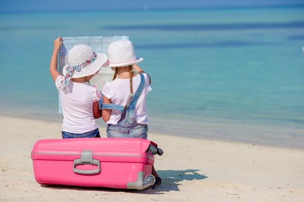Kleine touristenmädchen mit großem koffer auf tropischem weißem strand