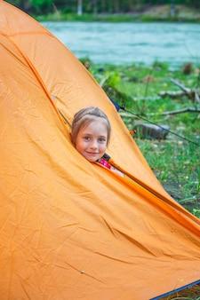 Kleine touristin schaut aus dem orangefarbenen zelt