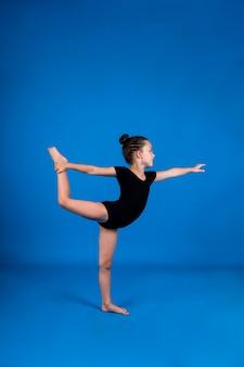 Kleine turnerin in einem schwarzen badeanzug dehnt sich auf blauem hintergrund mit einer kopie des raumes