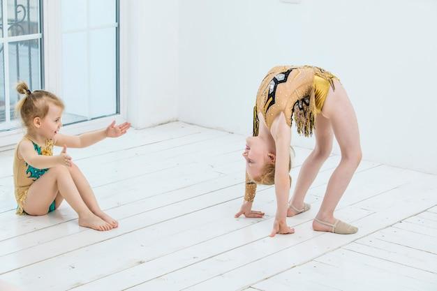 Kleine turnerin-mädchenmädchen und tänzerin, die sich im hellen raum glücklich und niedlich ausdehnt