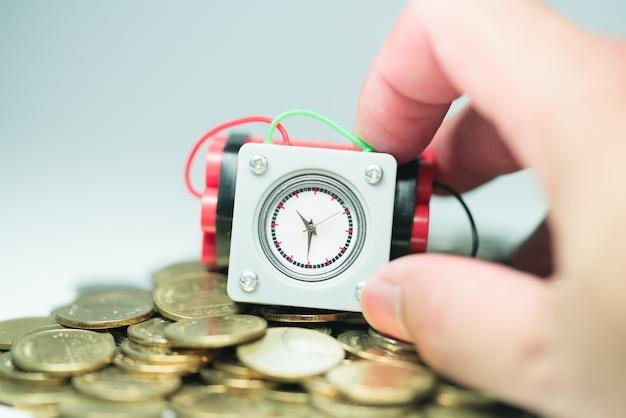 Kleine uhrbombe, die durch mann hält, überreichen stapel von münzen.