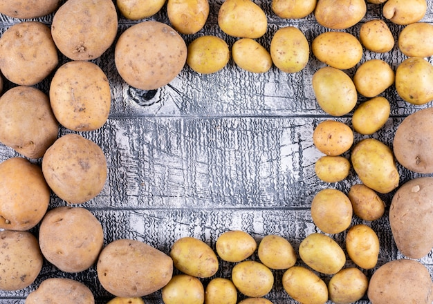 Kleine und große kartoffeln auf einem dunklen holztisch
