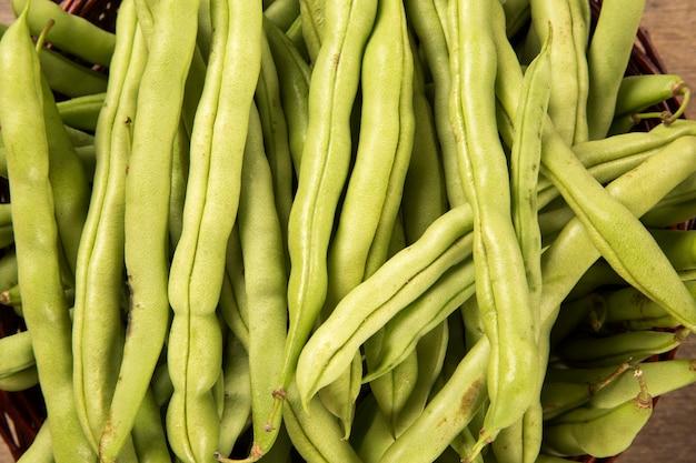 Kleine und schlanke grüne bohnen (haricot vert) auf einem holz. frisches gemüse.