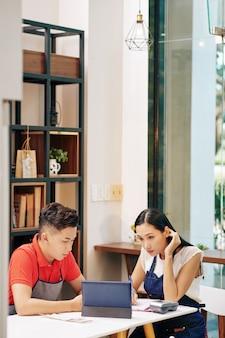 Kleine vietnamesische cafébesitzer, die mit finanzdokumenten arbeiten und an der strategie der geschäftsentwicklung arbeiten