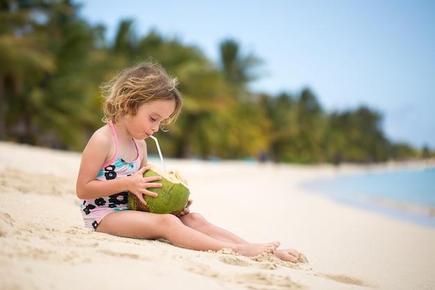Kleine vorschulkindfrau, die kokosnusssaft am ozeanstrand trinkt