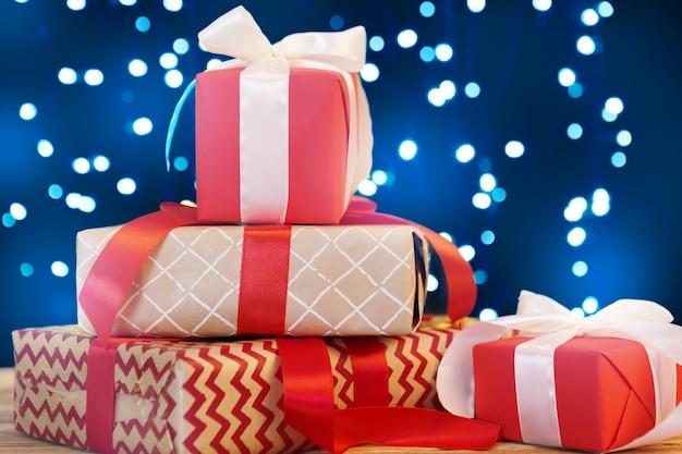 Kleine weihnachtsgeschenkboxen auf holztisch gegen bokeh lichter