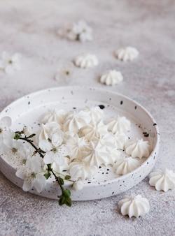 Kleine weiße baiser in der keramikschale auf betonhintergrund