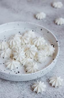 Kleine weiße baiser in der keramikschale auf betonoberfläche