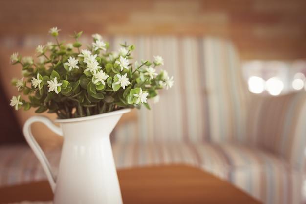 Kleine weiße blume im vase auf holztisch