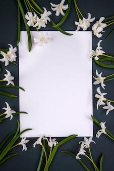 Kleine weiße frühlingsblumen chionodoxa und ein stück papier auf einem dunkelgrünen hintergrund mit kopienraum