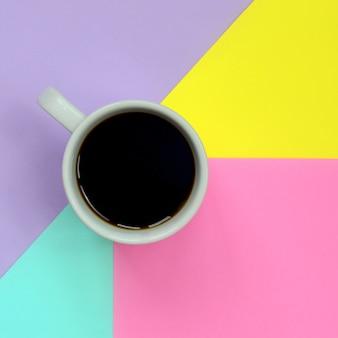 Kleine weiße kaffeetasse auf beschaffenheitshintergrund der blauen, gelben, violetten und rosa pastellfarbenpapier der mode im minimalen konzept