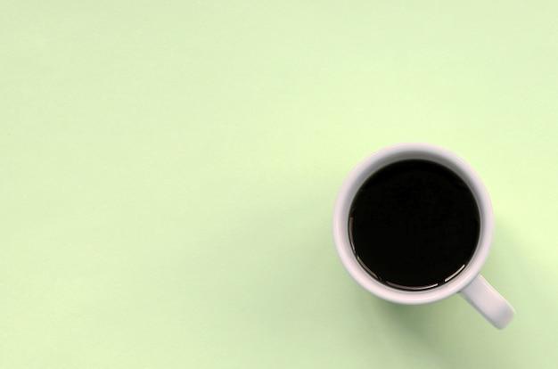 Kleine weiße kaffeetasse auf beschaffenheitshintergrund des modepastellkalk-farbpapiers