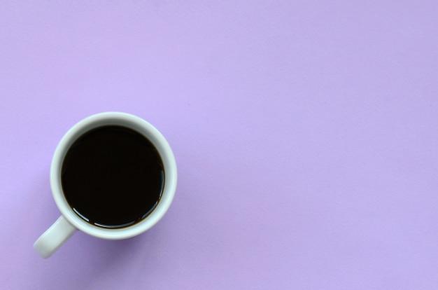Kleine weiße kaffeetasse auf beschaffenheitshintergrund des modepastells