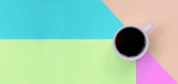 Kleine weiße kaffeetasse auf beschaffenheitsoberfläche des modepastellrosa-, blau-, korallen- und kalkfarbpapiers