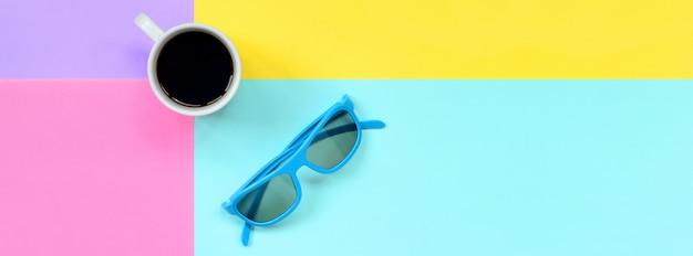 Kleine weiße kaffeetasse und blaue sonnenbrille auf beschaffenheitshintergrund des modepastellblaus