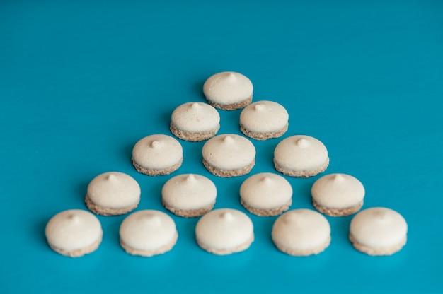 Kleine weiße kekse sind in form eines dreiecks auf blau angeordnet