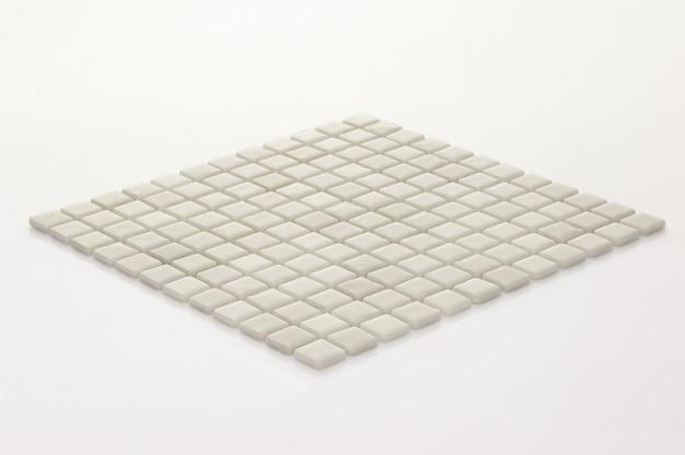Kleine weiße keramikfliese auf hellem hintergrund, majolika. für den katalog