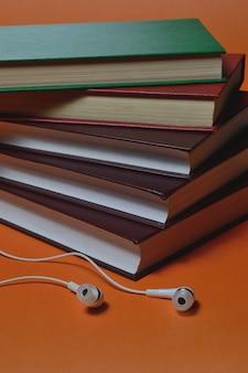 Kleine weiße kopfhörer und ein stapel bücher auf einem orangefarbenen hintergrund.