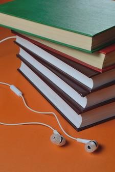 Kleine weiße kopfhörer und ein stapel bücher auf orangem hintergrund.