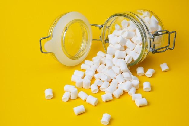 Kleine weiße marshmallows für dekoration und getränke und dekoration von kuchen in einem glas auf gelbem hintergrundkopierraum
