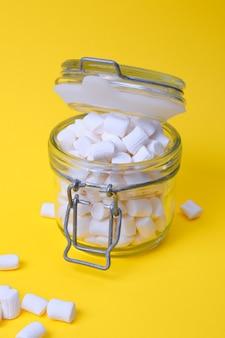 Kleine weiße marshmallows in einem glas auf einem gelben hintergrundkopierraum
