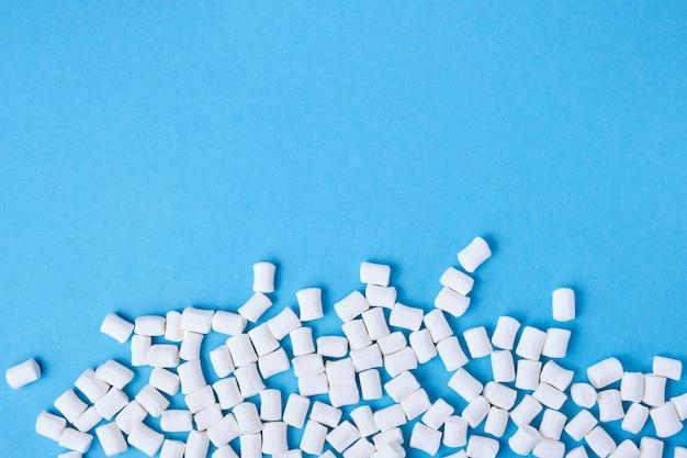 Kleine weiße marshmallows verstreut auf einem blauen hintergrundkopierraum