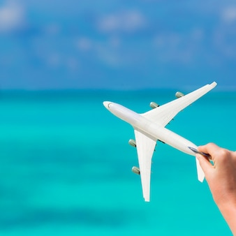 Kleine weiße miniatur eines flugzeuges auf hintergrund von türkismeer