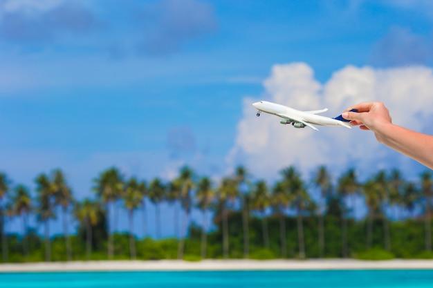 Kleine weiße miniatur eines flugzeuges auf türkismeer
