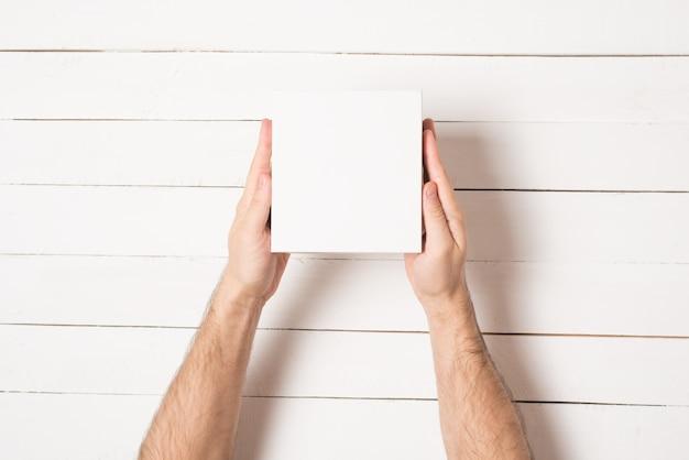 Kleine weiße pappkartons in männlichen händen
