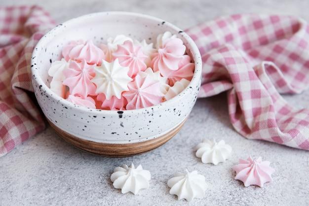 Kleine weiße und rosa baiser in der keramikschale auf betonoberfläche