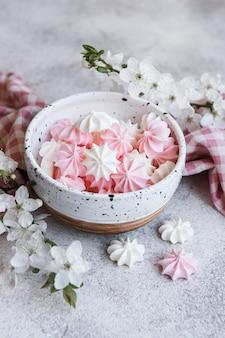 Kleine weiße und rosa baisers in der keramikschale auf betonoberfläche