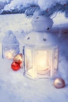 Kleine winterlaternen draußen auf einem weihnachtsbaum unter schnee.