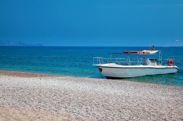 Kleine yacht für ausflug am kieselstrand in rhodos, griechenland