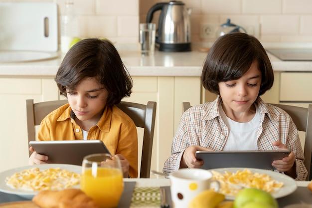 Kleine zwillinge, die auf ihrem tablet spielen