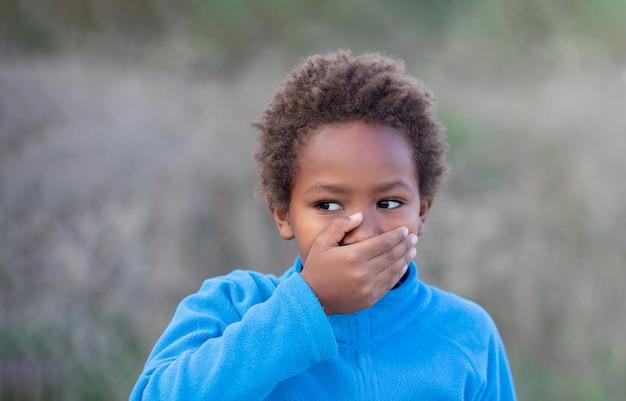 Kleiner afrikanischer junge, der seinen mund bedeckt
