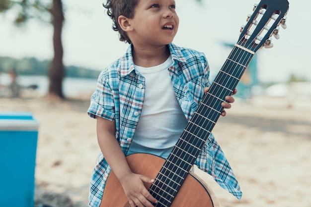 Kleiner afroamerikanischer lockiger junge auf sandy river beach.