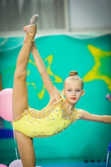 Kleiner aktiver schöner turner in wettbewerben der rhythmischen gymnastik