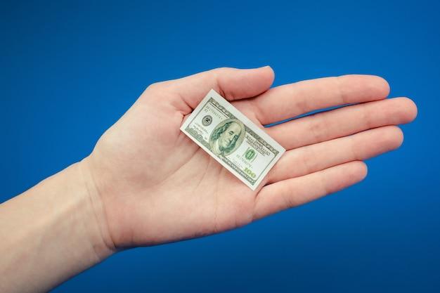 Kleiner amerikanischer dollarschein in der hand auf einem blauen hintergrund