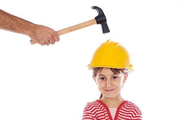 Kleiner arbeiter mit einem hammer und einem sturzhelm auf ihrem kopf