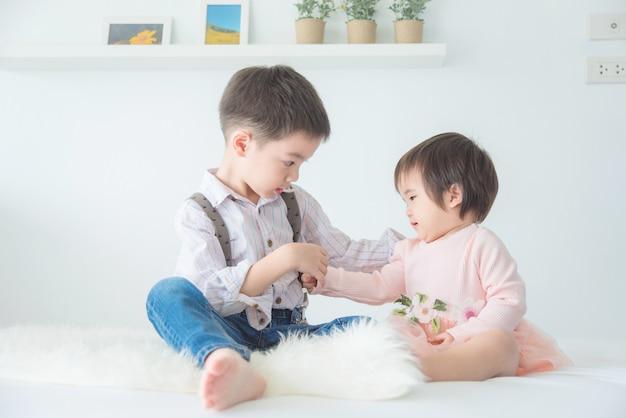 Kleiner asiatischer bruder, der zu hause mit seiner schwester auf bett sitzt