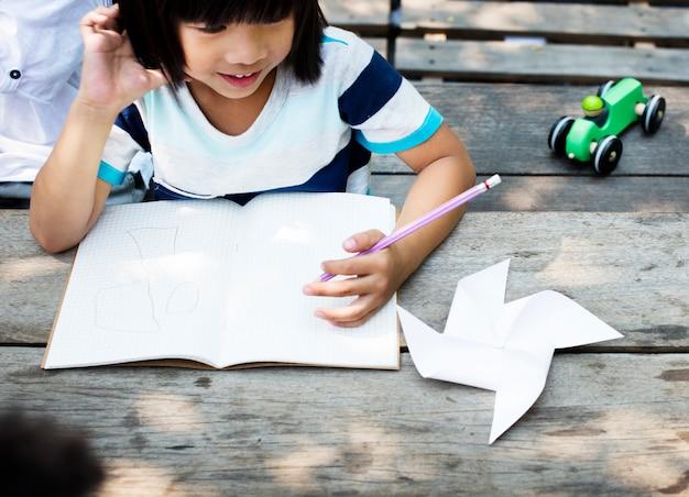 Kleiner asiatischer junge, der auf notizbuch zeichnet