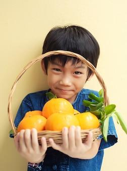 Kleiner asiatischer junge, der einen korb von großen frischen mandarinen-früchten hält