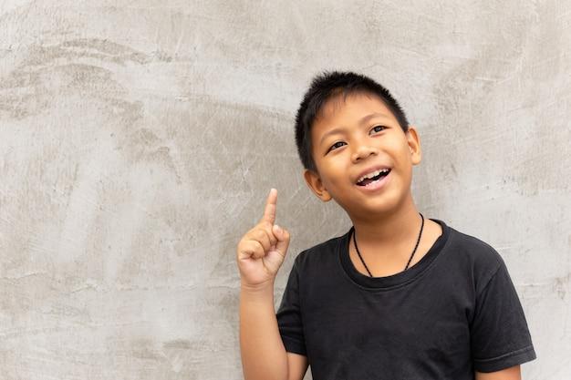 Kleiner asiatischer junge, der mit dem finger aufwärts lächelt lächelt.