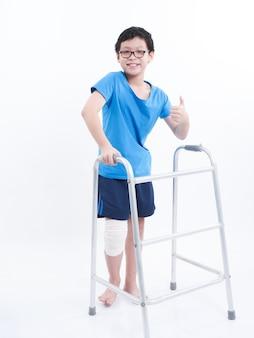 Kleiner asiatischer junge, der sich daumen herauf zeichen zeigt und wanderer allein über weißem bacground verwendet.