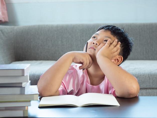 Kleiner asiatischer junge, der zu hause neue ideen in den hausaufgaben denkt
